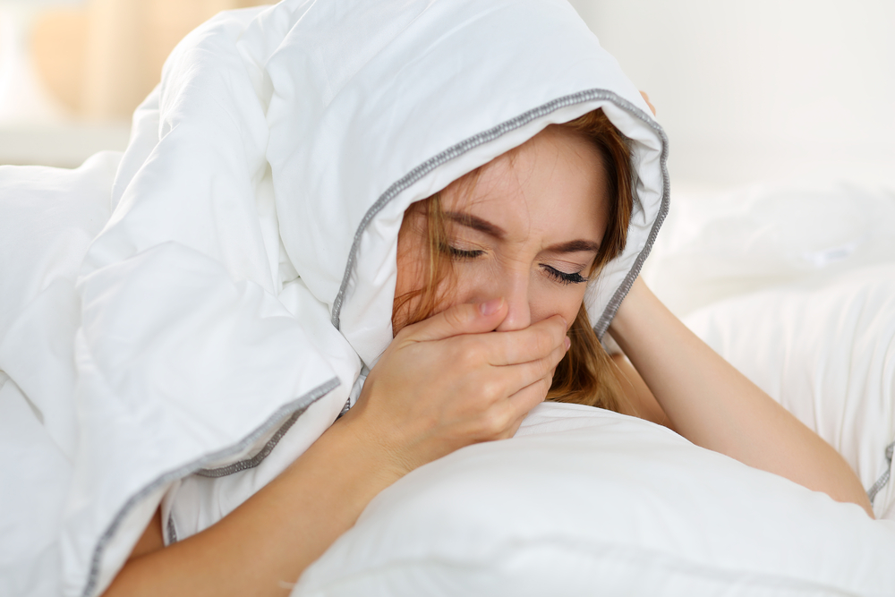 woman lying in bed suffering from morning sickness
