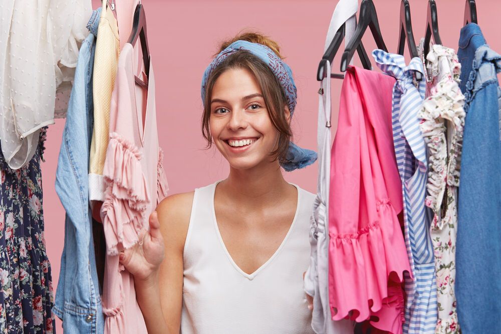 smiling woman wearing white T-shirt and scarf, looking through clothes rail while standing in her fitting room
