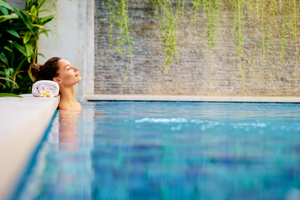 woman relaxing in outdoor spa swimming pool
