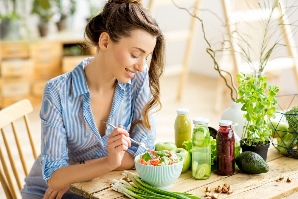 woman eating healthy salad to avoid hypothalamic amenorrhea