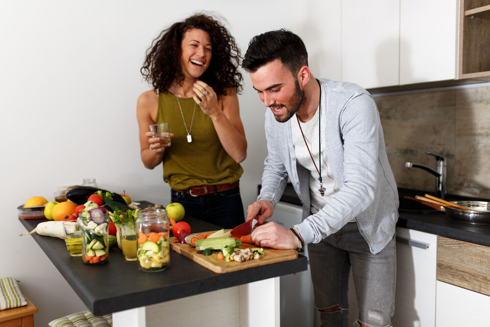 A young couple cooking vegan fast food at home