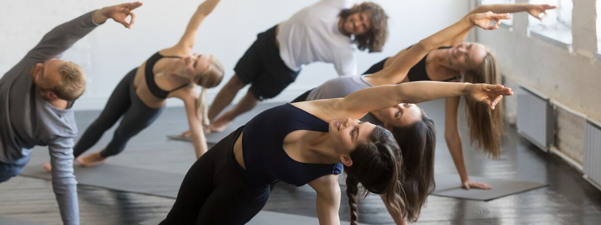 A group of people practicing vinyasa yoga
