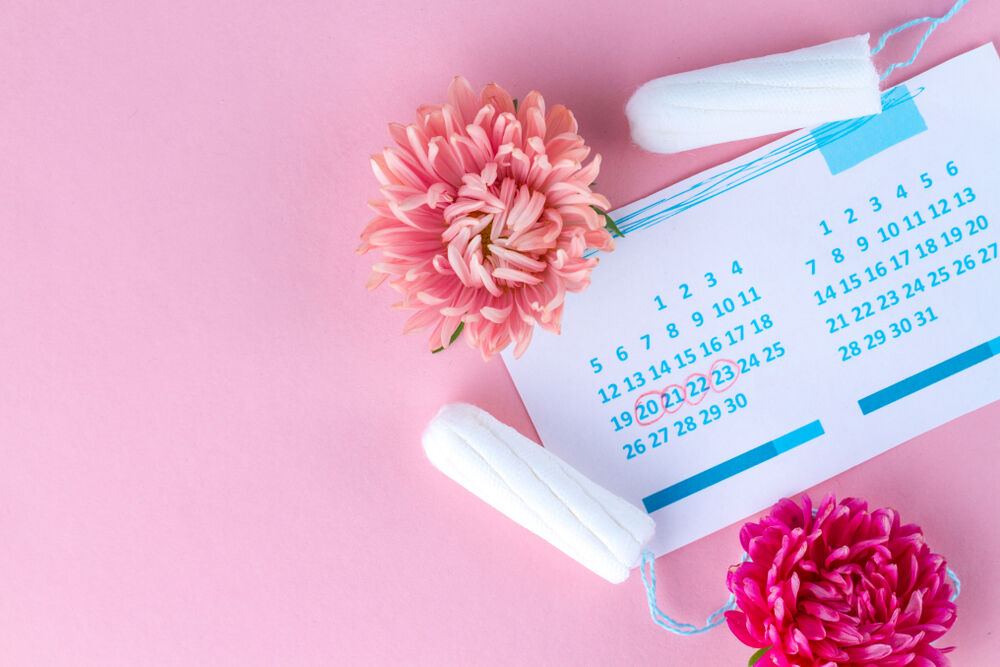 Tampons for menstruation, women's calendar and flowers on a pink background