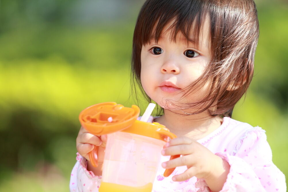 A baby drinking from a sippy cup with a straw