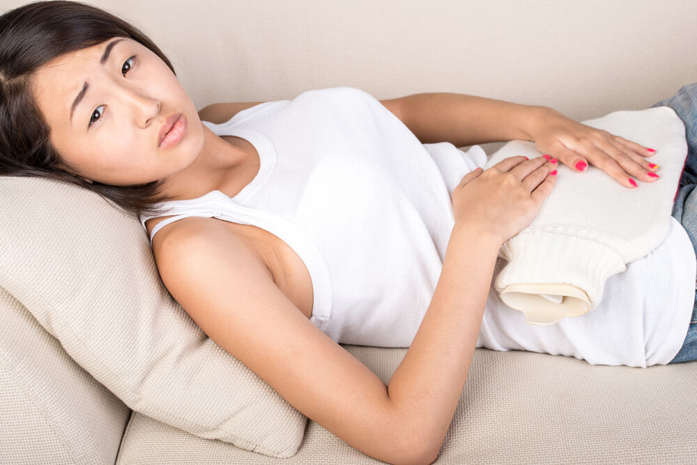 asian young woman is holding a heating pad on the abdomen.