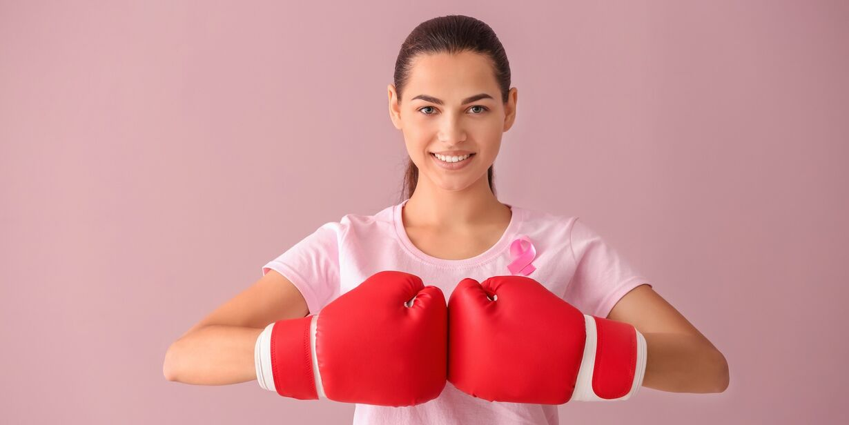 woman with pink ribbon and boxing gloves