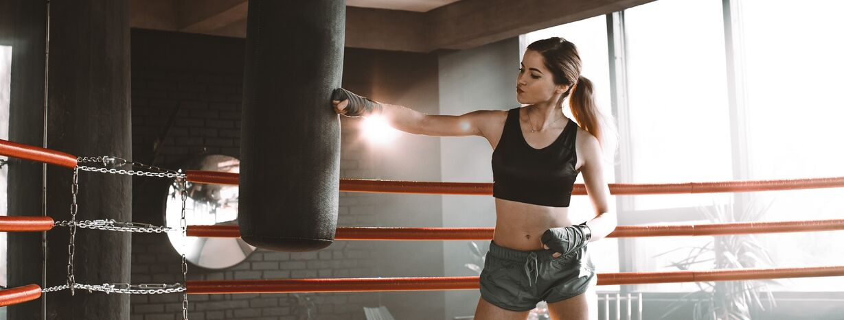 A woman boxing against a heavy bag