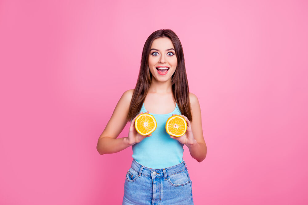 A girl holding two oranges as a depiction of breast pain