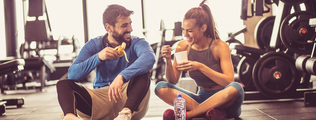 A man and woman eating after a workout