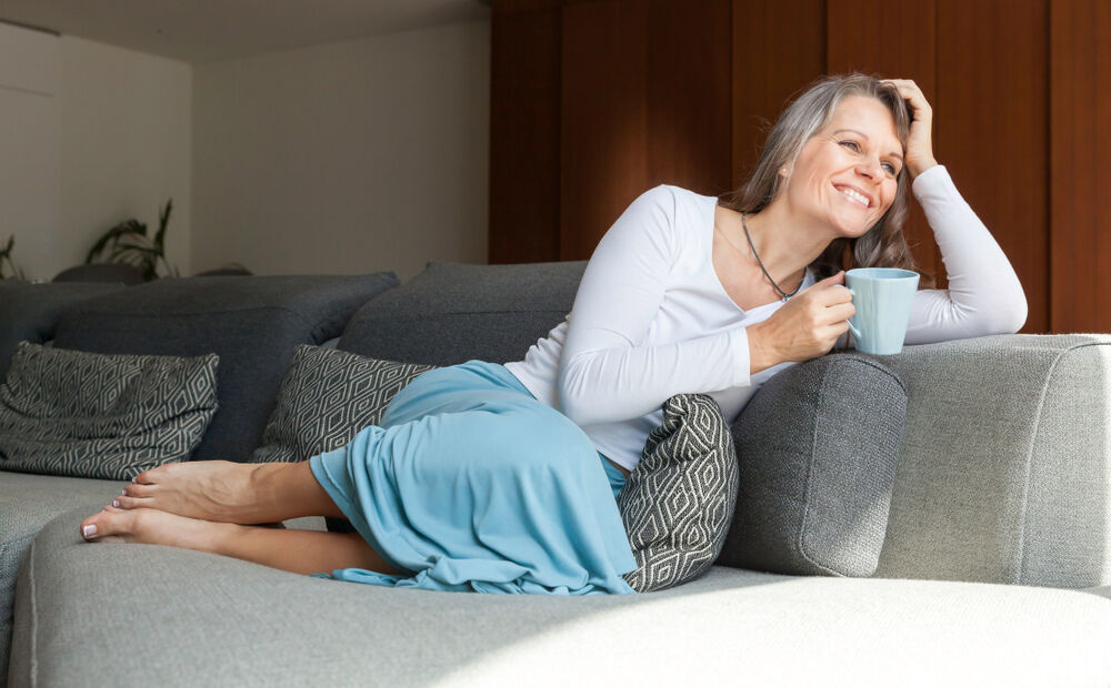 A woman relaxing on the couch to reduce menopausal fatigue