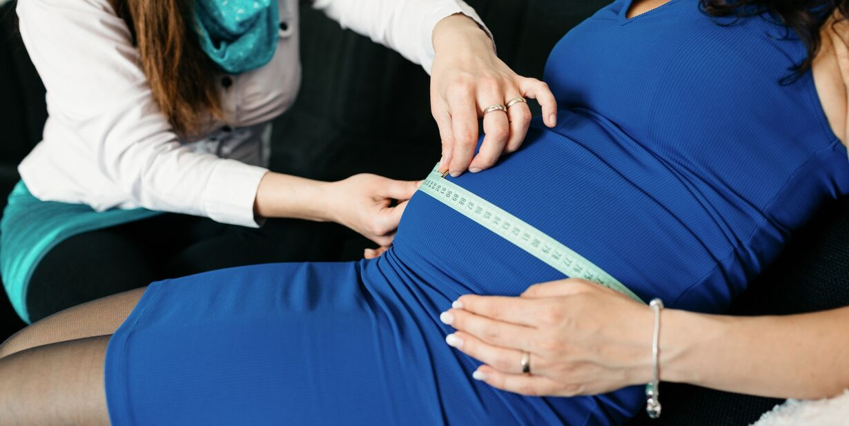 Doula measuring a belly of a pregnant woman