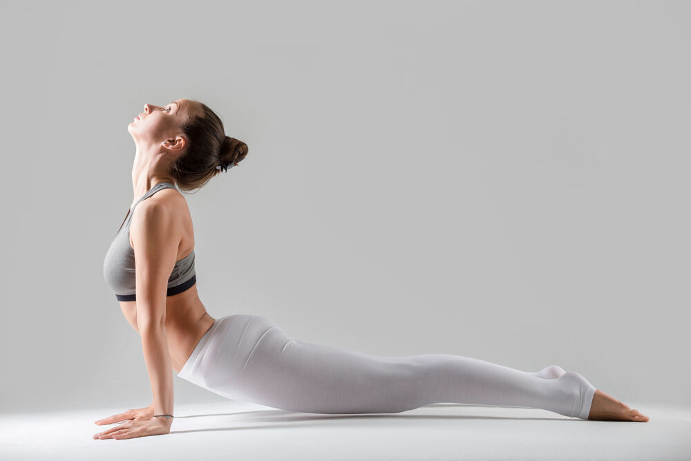 woman practicing yoga, standing in upward facing dog exercise