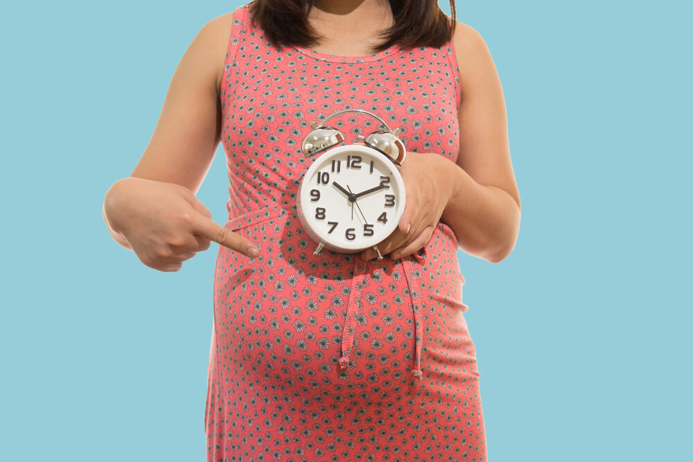 Pregnant woman holding clock. It's time. on blue background soft color