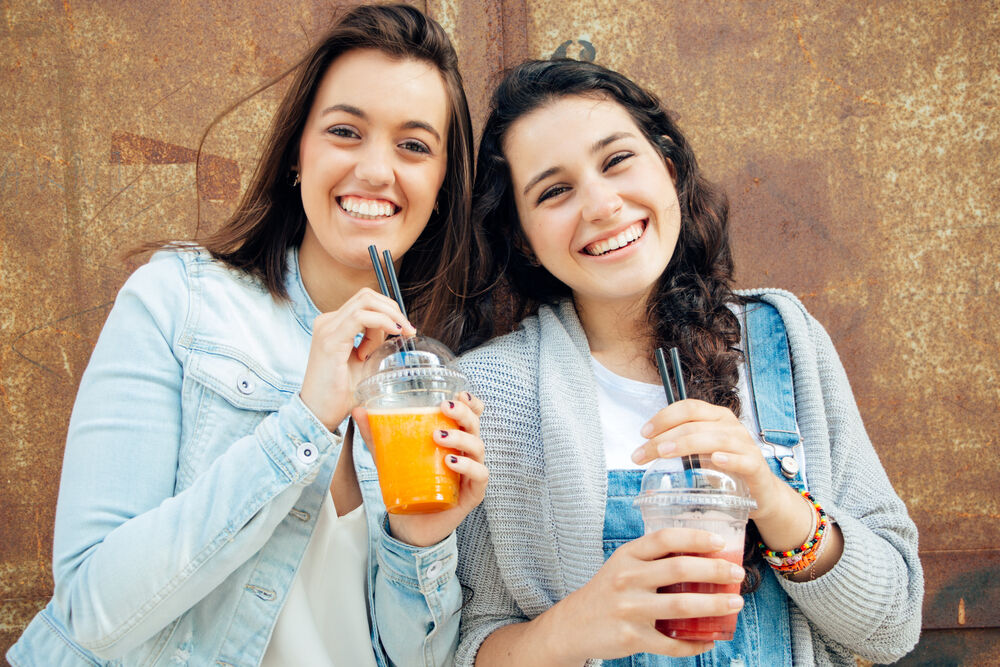 Girls drinking smoothies, which are a healthy snack to keep at home