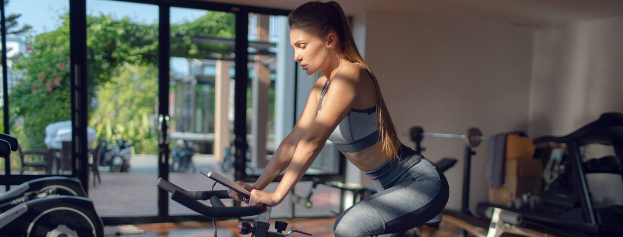 A woman exercising on a stationary bike at home