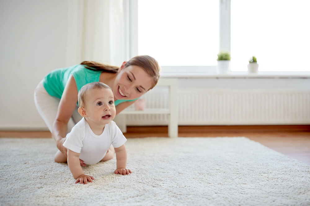A woman is helping her baby to start crawling