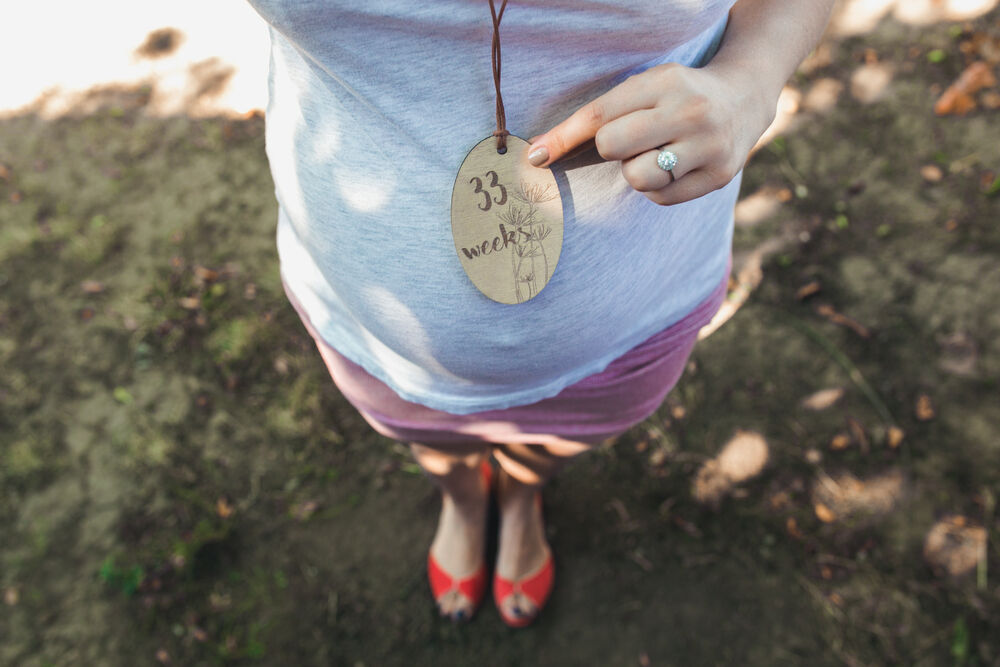Pregnant woman's belly with a close angle in the park