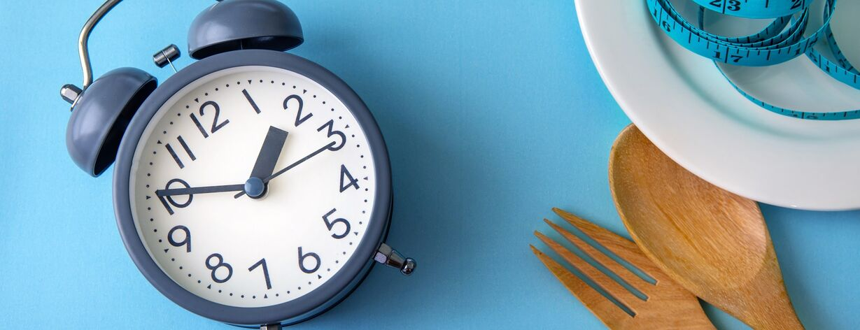 An alarm clock and kitchen utensils symbolizing fast metabolism