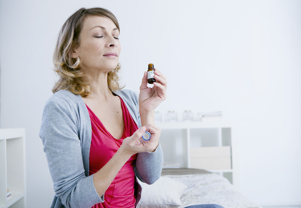 A woman holding an essential oil for hot flashes