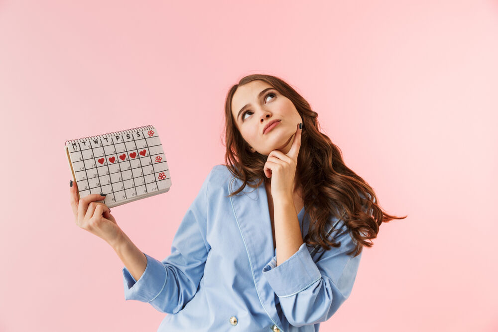 A confused woman holding a menstrual calendar wondering how late a period can be without being pregnant