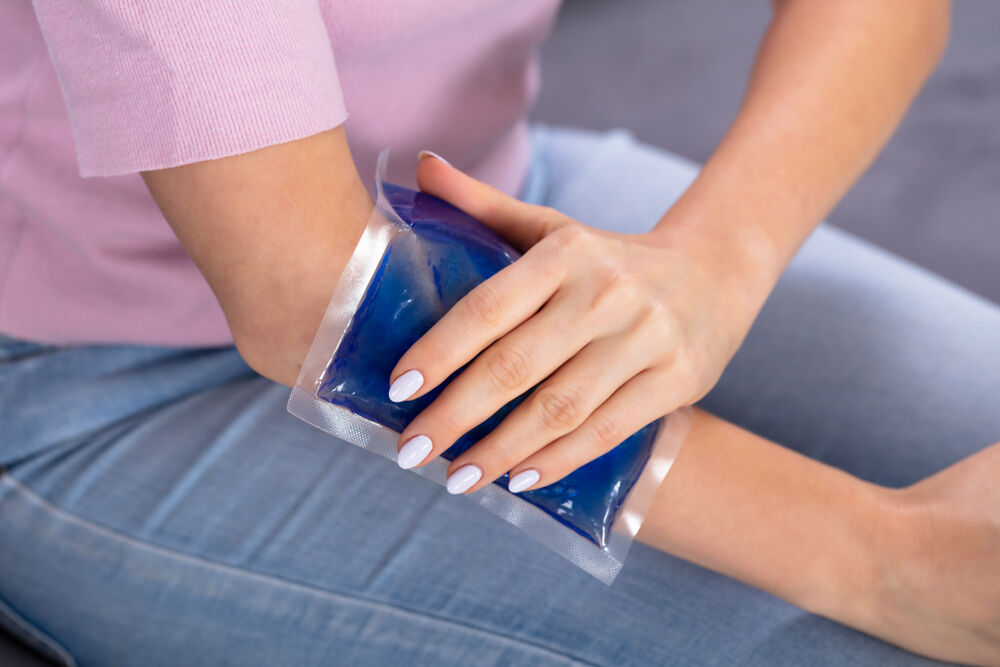A woman applying an ice pack over the bruise to prevent side effects from a blood draw