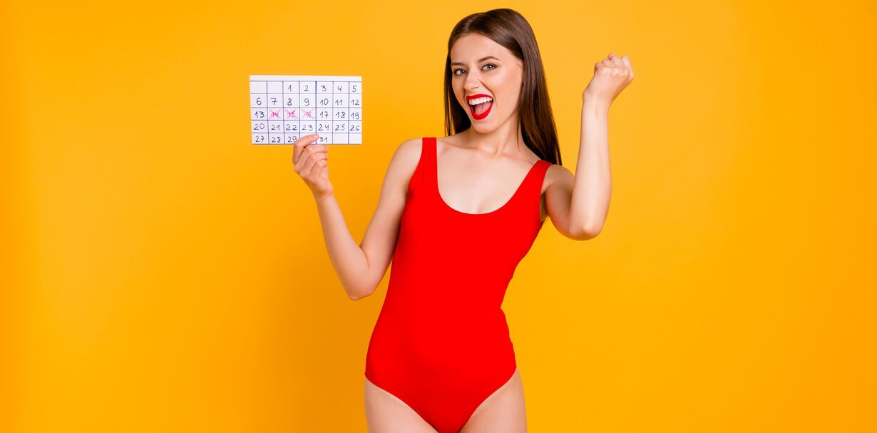 A woman wearing period swimwear and holding a menstrual calendar