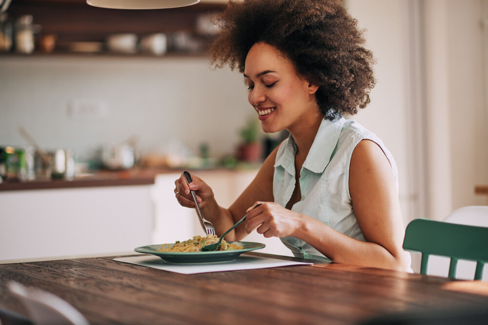 A woman with a fast metabolism eats pasta to gain weight