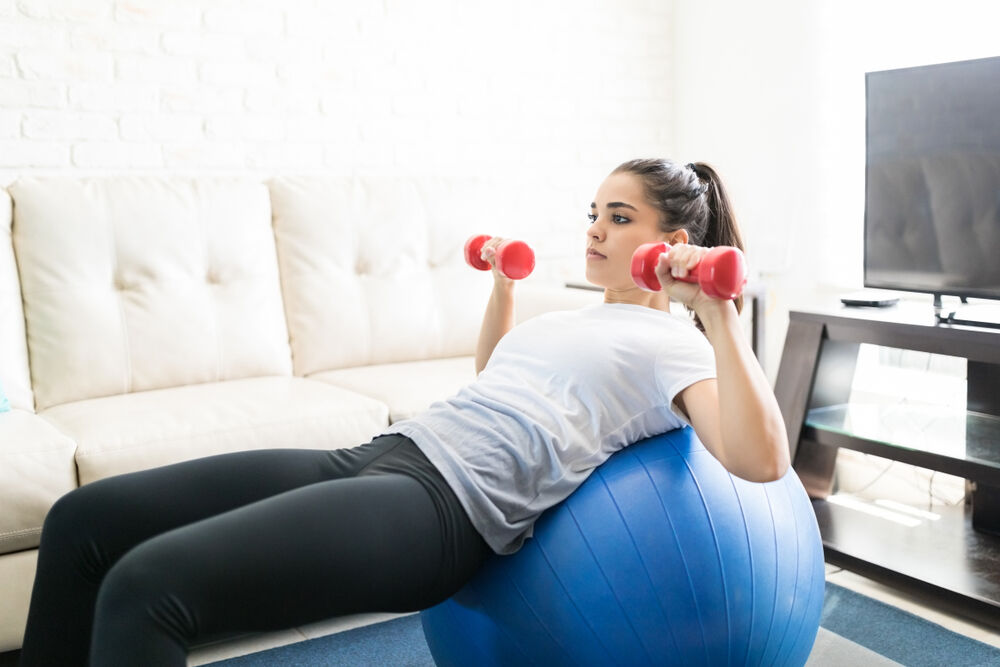 A woman doing stability ball exercises with weights